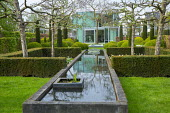 Yew hedge enclosing formal raised pond, pleached apple trees, cloud-pruned box hedges, view to house