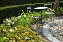 Chairs on stone and brick circular patio, epimedium foliage, narcissus