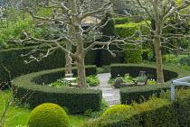 Circular yew hedges enclosing spring garden, chairs