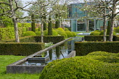 Yew hedge enclosing formal raised pond, pleached apple trees, cloud-pruned box hedges