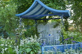 Blue oriental-style pavilion, hosta in container, table and chairs, salvia