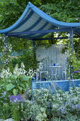 Blue oriental-style pavilion, hosta in container, table and chairs, salvia, eryngium