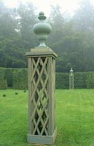 Urns on trellis plinths