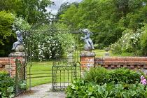 Wrought iron garden gate, brick wall, cherubs, bergenia leaves