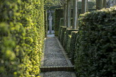 Hornbeam hedge, gravel path leading to sculpture on plinth
