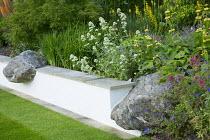 Large rocks set into low wall edging border, Centranthus ruber, geraniums