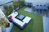 Outdoor Rattan furniture with cushions on contemporary roof terrace, astroturf, table and chairs on decking, barbecue