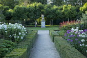 Formal borders egded with clipped box hedges, Cleome hassleriana, Persicaria amplexicaulis, phlox, view to stone sculpture on plinth