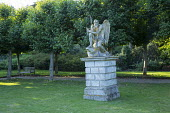 Father Time stone statue on plinth in front of lime tree avenue, wooden bench