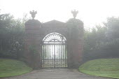 Ornamental cast iron gate into walled garden, brick piers with urns