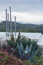 Contemporary aluminium sculpture, 'Towers of Time', in infinity pool, view to sea, Agave americana, Euphorbia characias subsp. wulfenii, Phormium tenax, Berberis thunbergii