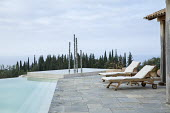 Contemporary aluminium sculpture, 'Towers of Time', in infinity pool, recliner chairs on stone terrace