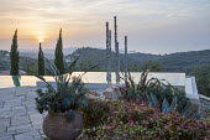 Aluminium sculpture, 'Towers of Time', in infinity pool at sunset, view to Cape Drastis, Strelitzia reginae and Euphorbia characias subsp. wulfenii in pot, Phormium tenax, Agave americana.
