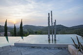 Aluminium sculpture, 'Towers of Time', in infinity pool at sunset, view to Cape Drastis