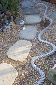 Stepping stone path through gravel, wavy rope