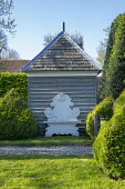 Ornate 'cut-out' bench against wooden shed, clipped box