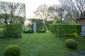 View to obelisk in low clipped box hedge enclosure, box balls in lawn, hornbeam hedges