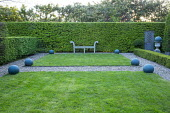 Wooden bench against hornbeam hedge, balls on square lawns, gravel paths