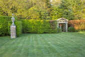 View across lawn to bust on plinth under timber arbour, beech hedge, urn on plinth