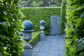 Stone patio, balls in stone urns, hornbeam hedges, low clipped box hedge