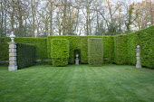 Formal garden, view across lawn to urn in niche in hornbeam hedge