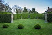 Row of clipped box balls in lawn, hornbeam hedges, urns on stone piers