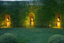 Formal garden, large box balls in lawn, lit urns on plinths in niches in hornbeam hedge