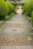 Brick steps, millstone set in brick paving, large clipped box shrubs underplanted with geraniums, view to moongate