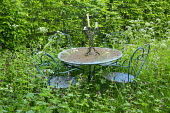 Rustic metal table and chairs in drift of Geranium phaeum