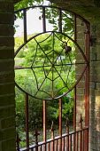 Metal gate with spider web design, brick wall