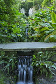 Stone bridge over waterfall, rill stream through border, Gothic wooden chairs