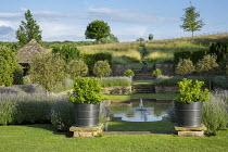 Formal pool and fountain in sunken garden, Lavandula angustifolia 'Princess Blue', standard Malus 'Evereste' trees, Viburnum tinus in large containers