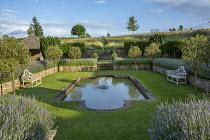 Formal pool and fountain in sunken garden, Lavandula angustifolia 'Princess Blue', stone wall, wooden Lutyens benches, standard Malus 'Evereste' trees