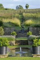 Formal pool and fountain in sunken garden, Lavandula angustifolia 'Princess Blue', Viburnum tinus in large containers