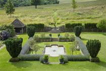 Overview of formal sunken garden surrounded by Lavandula angustifolia 'Princess Blue' borders, Malus 'Evereste' standards, pond