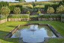 Formal pool and fountain in sunken garden, Lavandula angustifolia 'Princess Blue', standard Malus 'Evereste' trees