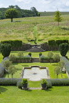Overview of formal sunken garden surrounded by lavender borders, Malus 'Evereste' standards, pond