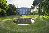 Circular pool in lawn in front of house, reflection