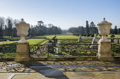 View from terrace over formal parterre garden, classical stone urns on plinths