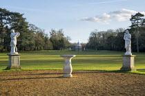 View across lawns to Archer Pavilion, classical statues on stone plinths