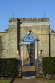Metal gateway between stone urn-topped piers, yew hedge, archway in high wall