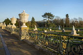 Stone urns and iron railings on terrace, view over formal parterre