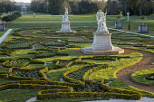 View across formal parterre garden, classical stone statues on plinths