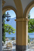 Tables and chairs on mediterranean garden terrace by Lake Como
