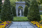Large bay pyramids, pansy bedding, ivy groundcover, view towards stone statue under arch, Shepherd's Gate