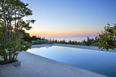 Formal swimming pool terrace, view across sea to sunrise, Lagerstroemia indica, Pierre de Bourgogne stone paving