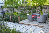 Stackable outdoor chairs by Dedon on Ipe hardwood decking, Trachelospermum jasminoides on brick wall, stepping stone path interspersed with pebbles, barbecue, pleached hornbeam screen, Myrtus communis...