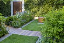 Cedar wood path across lawn, mowing strip, Geum 'Totally Tangerine', Iris 'Tamberg', Euonymus alatus 'Compactus', Portland cement concrete border edging, Cor-Ten steel wall