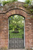 Wrought iron gate under brick arch