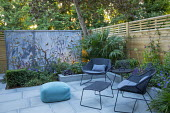 Small courtyard garden at dusk, contemporary chairs and table by Cane Line on sawn grey Yorkstone patio, galvanised steel screen by Steel Sculptures, Chamaerops humilis
